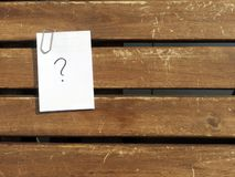 Question mark on a wooden table. Question sign on a notebook with a paperclip on a wooden table on a sunny day stock photos