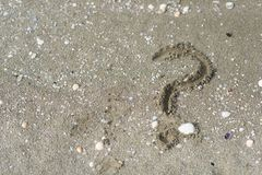 Question mark wriiten on a sandy beach. Concept of faq, travel tips and travel destinations stock photography