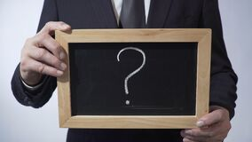 Question mark written on blackboard, business person holding a sign in hands. Stock footage stock footage