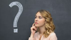 Question mark written on blackboard, pensive woman thinking, making decision stock footage