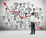 Question marks and arrow on wall. Businessman looking at drawing question marks and arrow on wall Royalty Free Stock Photo