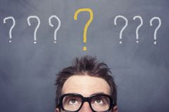 Question Marks. Businessman lookip up question marks on blackboard stock photos