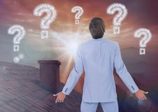 Question marks and Businessman standing on Roof with chimney and epic twilight sunset. Digital composite of Question marks and Businessman standing on Roof with Royalty Free Stock Photos