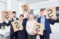Question marks for doubt. Business team holds question marks for doubt Royalty Free Stock Images