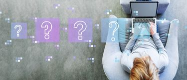 Question marks with man using a laptop stock image