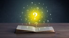 Question marks over book. Yellow question marks hovering over open book Royalty Free Stock Photography