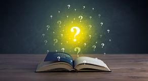 Question marks over book. Yellow question marks hovering over open book Royalty Free Stock Images