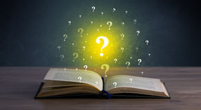 Question marks over book Royalty Free Stock Photo
