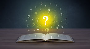 Question marks over book. Yellow question marks hovering over open book Stock Photography