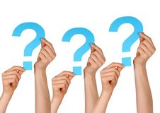 Question marks. Some blue question marks holding by hands, isolated Stock Image