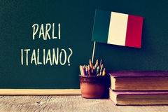 Question parli italiano? do you speak Italian?. A chalkboard with the question parli italiano? do you speak Italian? written in Italian, a pot with pencils, some Royalty Free Stock Photos