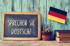 Question sprechen sie deutsch? do you speak german?. A chalkboard with the question sprechen sie deutsch? do you speak german? written in german, a pot with Stock Image