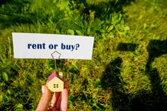 The question to Buy or Rent,typed on a scrap of lined paper and house model in female hand. A decision aided by analysis stock images