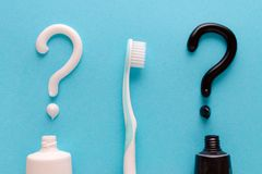 Question from white and black toothpaste, teeth care concept, toothbrush on blue background. Flatlay stock image
