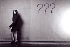 Question. Young girl against the old wall with graffiti. toned black and white image Royalty Free Stock Photography