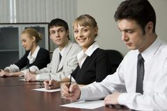 Questioning. Successful young people are sitting at the table and filling a forms Royalty Free Stock Image