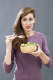 Questioning 20s girl questioning the taste of a mixed green salad Stock Photo
