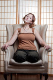 Questioning woman. A beautiful young woman sits in a yoga position at home after meditating Stock Photo
