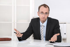 Questioningly bald engineer or specialist sitting at desk. Royalty Free Stock Image