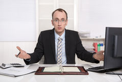 Questioningly bald engineer or specialist sitting at desk. Royalty Free Stock Images