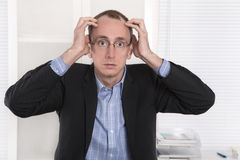 Questioningly bald engineer or specialist sitting at desk. Stock Photos