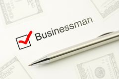 Questionnaire: businessman choice, marked checkbox with a silver pen on paper and dollars background. Careers survey. Concept Royalty Free Stock Images