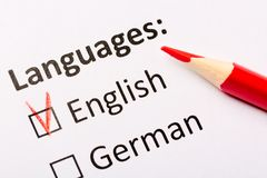 Questionnaire concept. Languages with English and German checkboxes with red pencil. Close up image.  Royalty Free Stock Photos