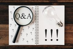 Questions and answers concept Q&A. Magnifying glass, notebook and bulb with question mark and exclamation symbol on wooden table royalty free stock images