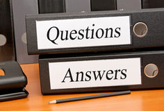 Questions and Answers. Two black binders labeled with questions and answers next to pencil on wood desk Royalty Free Stock Images