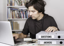 Questions and Answers - two folders on office desk. Man working. On notebook Royalty Free Stock Photography