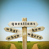 Questions and answers. Wooden sign with addresses questions and roads on the horizon Stock Photo
