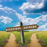 Questions and answers. Wooden sign with directions of the questions and answers and two roads on the horizon Stock Photos