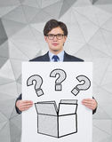 Questions in the box. Businessman holding poster with questions in the box Stock Photos