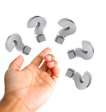 Questions concept. Hand and question marks around sign Royalty Free Stock Photo