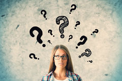 Questions concept. Pretty caucasian girl with question marks on concrete wall background. Questions concept stock images