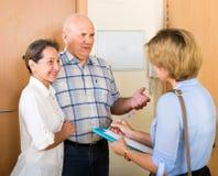 Questions de réponse de couples d'employé dans la porte Photo stock