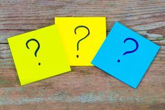 Questions, decision making or uncertainty concept - a pile of co. Lorful sticky notes with question marks on wooden background Royalty Free Stock Image