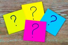 Questions, decision making or uncertainty concept - a pile of co. Lorful sticky notes with question marks on wooden background Stock Photo