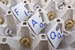 Questions. Frequently asked questions (FAQ) abbreviation in a form of puzzle letters inside of an egg tray with golden and silver question marks made of royalty free stock photography