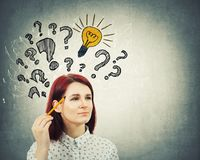 Questions and idea. Young pensive woman holding pencil pointed to head drawing interrogation marks light bulb and arrow mess. Question and idea concept stock images