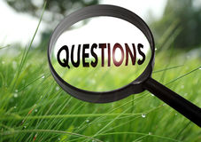 Questions. Magnifying glass with the word questions on grass background. Selective focus Royalty Free Stock Photos