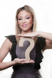 Questions mark. Woman holding up a questions mark model to her chest stock image