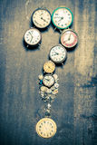 Questions mark arranged by clocks. On old wooden table stock images
