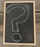Questions mark. Written in chalk on a chalkboard on a rustic background stock images