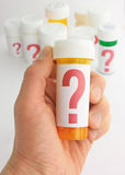 Questions about Medicine. Closeup of a hand holding a medicine bottle marked with a large question mark. In the background is a group of pill bottles all labeled Royalty Free Stock Images