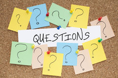 Questions. Note and question marks pinned on cork noticeboard Stock Photos