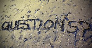 QUESTIONS with question mark written can be used for the end of. QUESTIONS with question mark written on the sand can be used for the end of business stock image