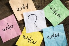 Questions and question marks on crumpled colored note papers on a wooden background.  stock photos
