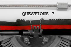 QUESTIONS text by the old typewriter on white paper royalty free stock photos