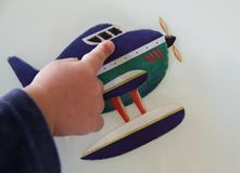 Questions from a toddler. Little boy`s hand showing detail of an airplane sticker. Conceptual image of the learning process and emotional development of toddlers royalty free stock photography